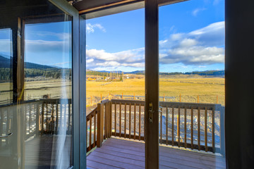 Glass door opens to a balcony with a beautiful view.