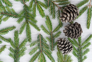 Top view of a Christmas wooden background made of fir branches and cones