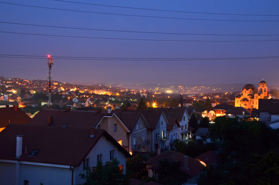 Houses with red roofs in suburban area while night is falling