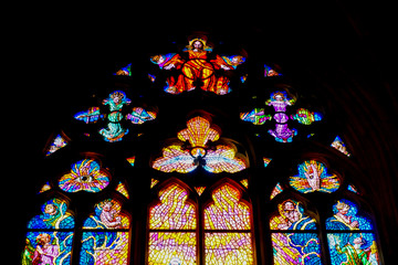 Stained glass windows with cross and icons in st. Vitus Cathedral, Prague. Concept of religious landmars in Czech Republic and Gothic style interior design.