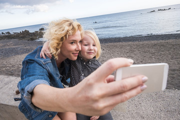cheerful mother and son blondes both stay together outdoor in leisure activity taking selfie pictures with smart phone tehnology ready to share it on social networks for friends away