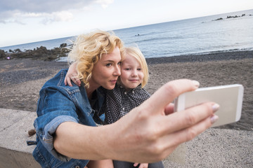 blonde woman and little blonde son take selfie picture with ocean and horizon in background. vacation lifestyle memories with new technology. happiness for young family outdoor