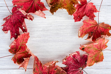 Top view of a circular frame on a wooden background of autumn leaves