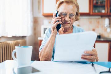 Elderly woman contacting custumer services after recieving a bill