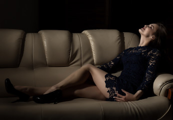Sensual attractive young woman in a lace dress poses on a sofa.