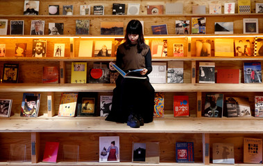 A woman reads a book at the Shinjuku branch of Book and Bed, an accommodation combined with book cafe where guests can sleep in hidden bunks built into a large bookshelf, during a photo opportunity in Tokyo