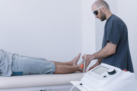 The physiotherapist treating a man using equipment for Lightning Laser