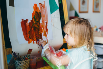 Portrait of adorable little girl drawing with paints and palette at easel
