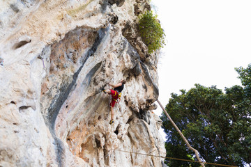 Young man rock climbing on white mountain in Thailand