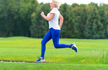 Happy healthy woman running through a park