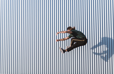 Young man with a cap and beard jumping in an acrobatics way on a sunny day of summer background an iron wall
