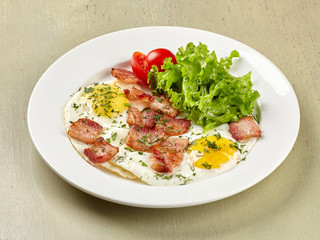 Scrambled eggs with bacon tomatoes and lettuce leaf.