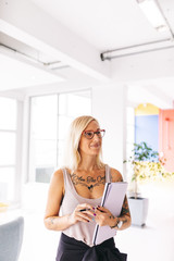 tattooed young businesswoman doing organization at work