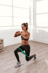 sporty woman doing warm up with elastic band in gym