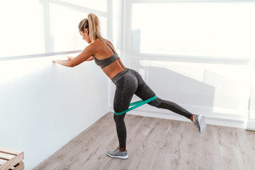 athletic young woman doing excercise with elastic band