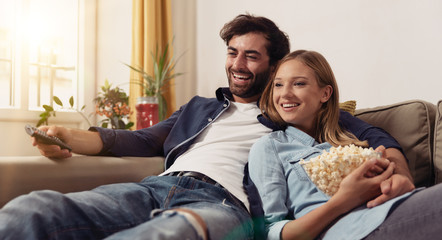 Couple watching TV on a sofa at home