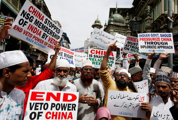 Protestors hold placards as they shout slogans during a protest against what they say is the Chinese government for detaining thousands of Uighur minority Muslims, at a street in Mumbai