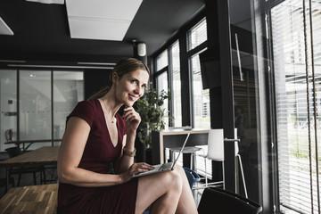 Smiling businesswoman in office wearing burgundy dress using laptop