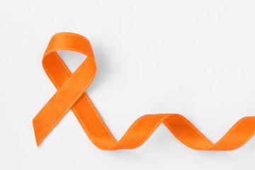 Orange ribbon on white background - Concept of leukemia awareness, kidney cancer association, multiple sclerosis and animal abuse