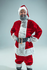 Smiling funny guy with christmas hat posing at studio. New Year Holiday. Christmas, x-mas, winter, gifts concept. Man wearing Santa Claus costume on gray. Copy space. Winter sales.