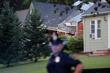 A police officer stands outside a home where a man died in a series of gas explosions in Lawrence