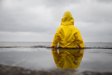 Rainy clouds. Child in a yellow raincoat.