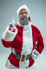 Funny guy with christmas hat posing at studio pointing up. New Year Holiday. Christmas, x-mas, winter, gifts concept. Man wearing Santa Claus costume on gray. Copy space. Winter sales.