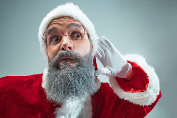 Funny eavesdropping guy with christmas hat posing at studio. New Year Holiday. Christmas, x-mas, winter, gifts concept. Man wearing Santa Claus costume on gray. Copy space. Winter sales.