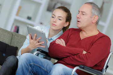 young woman trying father to use tablet