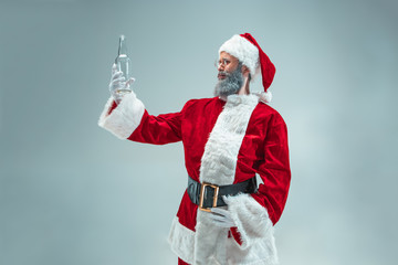 Funny guy with christmas hat posing at studio. New Year Holiday. Christmas, x-mas, winter, gifts concept. Man wearing Santa Claus costume on gray. Copy space. Winter sales.