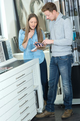 young couple of adults choosing ceramic tile for bathroom