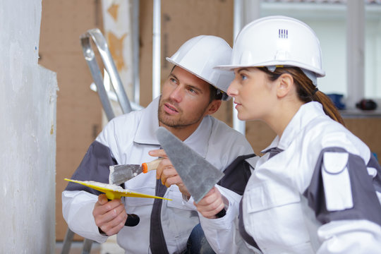 female and male plasterer at indoor wall renovation decoration