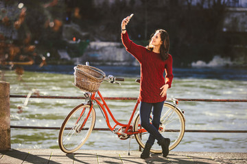 A beautiful young woman with a retro red bicycle is making a photo of herself in the old city of Europe on the River Rhine embankment in the Swiss city of Basel. Sunny warm day in winter