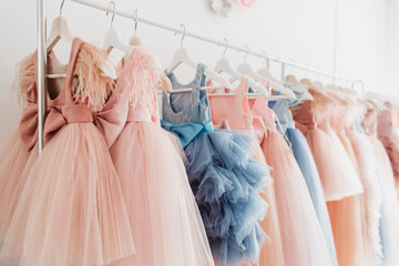 Beautiful dressy lush pink and blue dresses for girls on hangers at the background of white wall. Kids dresses with feathers for prom and holiday.