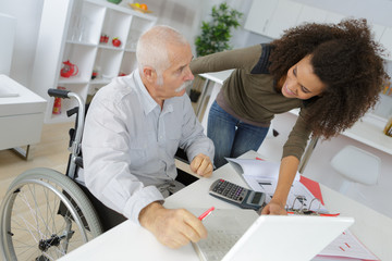 young lady helping wheelchair bound man to use computer