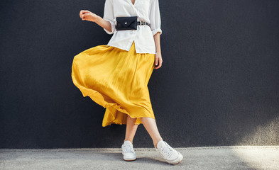 Horizontal cropped image of stylish slim woman in beautiful yellow skirt. Caucasian female fashion model standing over gray wall background outdoor with copy space. Wall mural