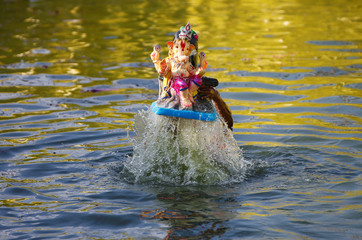 A devotee immerses an idol of the Hindu god Ganesh, the deity of prosperity, into a pond on the second day of the ten-day long Ganesh Chaturthi festival in Ahmedabad
