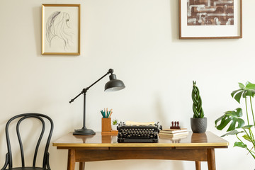 Framed drawing on a white wall above an antique, wooden desk with a vintage, black typewriter in a home office interior