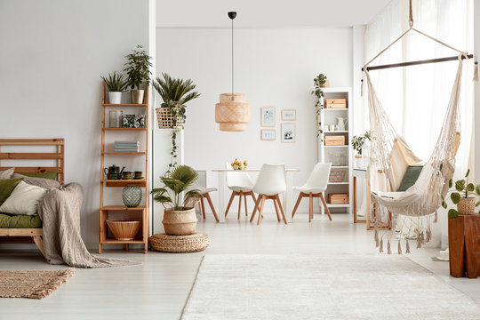 Hammock and plants in white apartment interior with lamp above dining table and chairs. Real photo