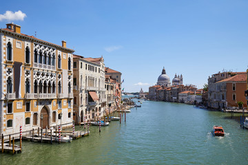 Grand Canal in Venice at midday with Saint Mary of Health basilica and motorboat in Italy