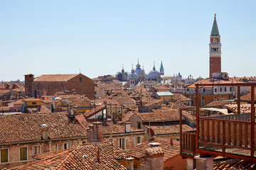Venice roofs view and San Marco basilica with bell tower and typical wooden altana balcony in a sunny day in Italy