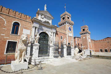 Arsenale di Venezia walls and white statues, clear blue sky in Venice, Italy