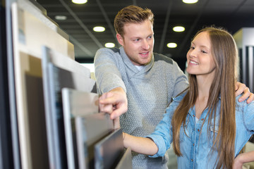 young happy couple looking at bathroom tile in furniture store