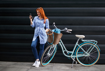 Female looking on cell phone next to bike