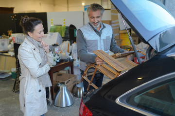 man helps customer to put furniture in her car