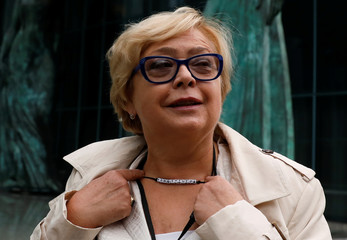 Supreme Court President Malgorzata Gersdorf points at her necklace with the word 'Constitution' as she arrives to the Supreme Court in Warsaw