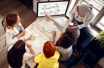 Afro-American girl present her idea on computer for new fashion creation to working team. Wall mural
