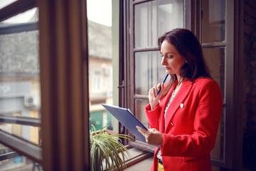 Woman occupied with job working near window