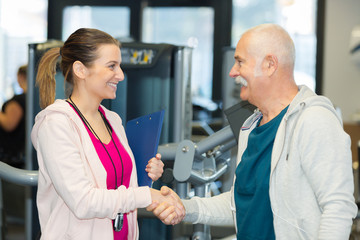 senior man hand-shacking his personal trainer in fitness studio