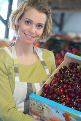 female worker holding cherries